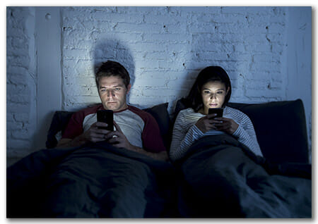 Couple on Bed looking at cell phones not each other