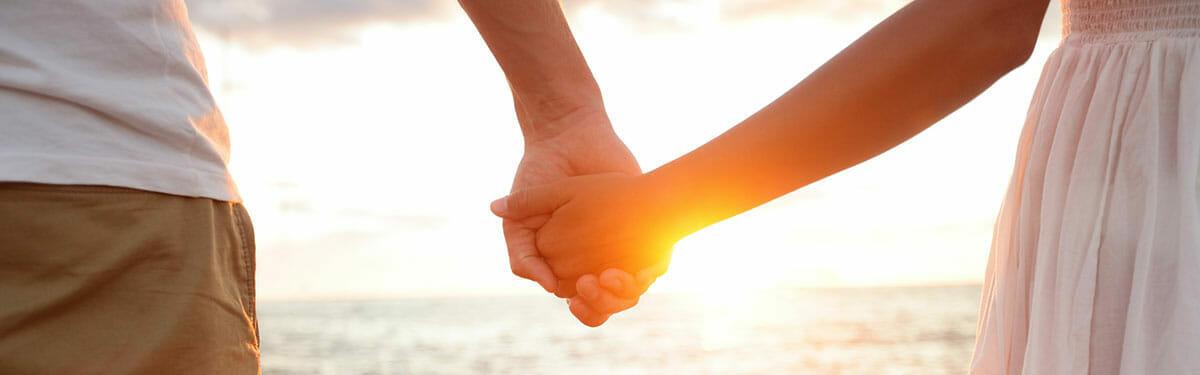 Couple Holding hands on beach as sun sets