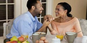 Couple smiling over healthy breakfast.